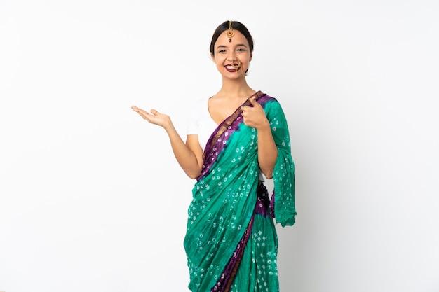 Jonge indische vrouw die op witte muur lege ruimte op de palm houden en met omhoog duimen
