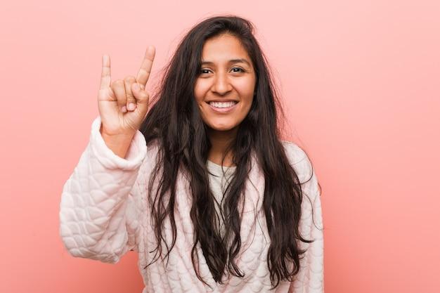 Jonge indische vrouw die pyjama draagt die een hoornsgebaar toont als revolutieconcept.