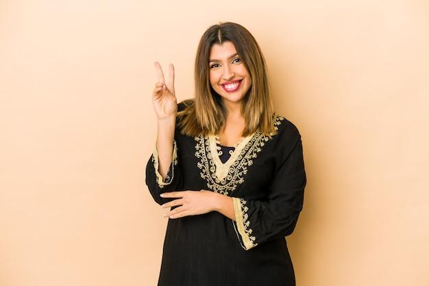 Jonge indische vrouw die traditionele geïsoleerde kleding draagt die nummer twee met vingers toont.