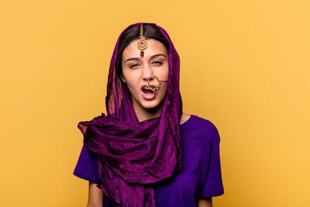 Jonge indische vrouw die traditionele sari-kleren draagt die op gele muur worden geïsoleerd die zeer boos en agressief gillen