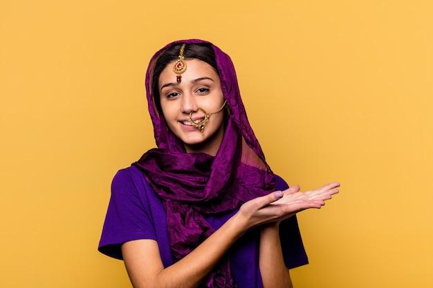 Jonge indische vrouw die traditionele sari-kleren op geel draagt die een exemplaarruimte op een palm houden.