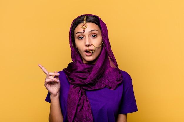 Jonge indische vrouw die traditionele sari-kleren op geel draagt die naar de kant wijzen
