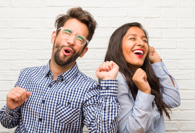 Jonge indische vrouw en kaukasisch man paar luisteren naar muziek, dansen en plezier hebben, verplaatsen, schreeuwen en geluk, vrijheid concept uiten