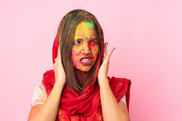 Jonge indische vrouw met kleurrijk holipoeder op haar gezicht op roze gefrustreerde muur en het behandelen van oren