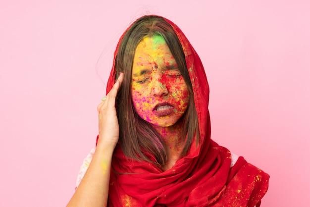 Jonge indische vrouw met kleurrijk holipoeder op haar gezicht op roze muur met hoofdpijn