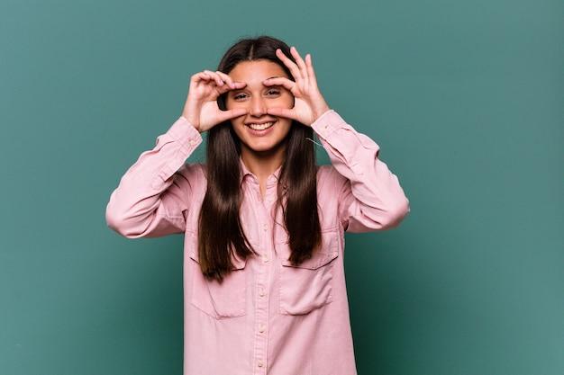 Jonge indische vrouw op blauw die ok teken over ogen toont