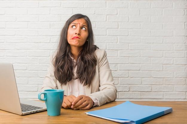Jonge indische vrouw op het kantoor die en verward twijfelen