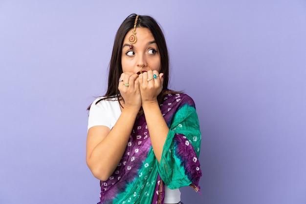 Jonge indische vrouw op purpere zenuwachtig en doen schrikken muur die handen aan mond zetten