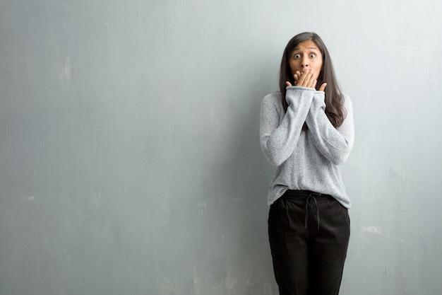 Jonge indische vrouw tegen een grungemuur die mond, symbool van stilte en onderdrukking behandelen, proberend om niets te zeggen
