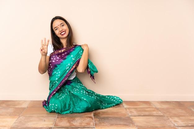 Jonge indische vrouwenzitting op de vloer gelukkig en tellend drie met vingers