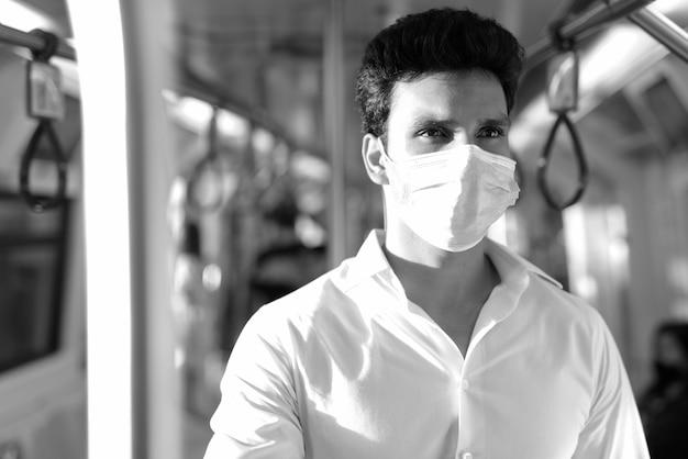 Jonge indische zakenman die masker draagt en zich met afstand binnen de trein in zwart-wit bevindt