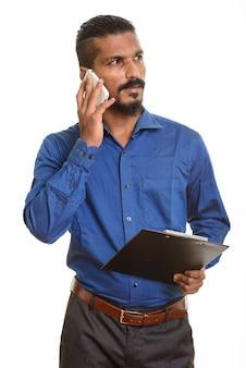 Jonge indische zakenman die op mobiele telefoon spreekt en klembord houdt terwijl het denken