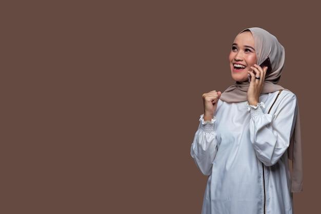 Jonge indonesische vrouw die hijab draagt, krijgt het goede nieuws op haar mobiel met een glimlach en succesvolle uitdrukking geïsoleerd op effen achtergrond