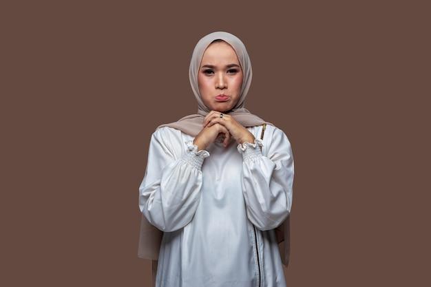 Jonge indonesische vrouw in hijab met droevige, bezorgde en teleurgestelde uitdrukking