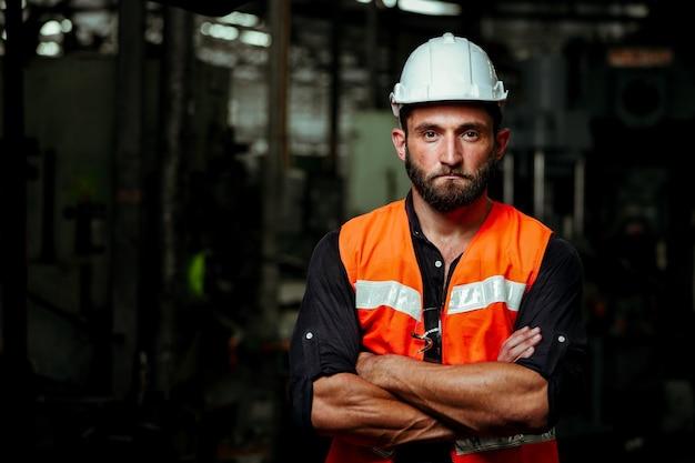 Jonge industriële werknemer man aan het werk met metalen machine in fabriek met veel apparatuur
