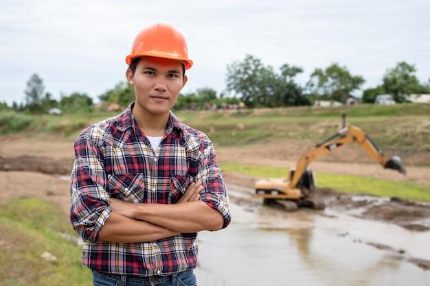 Jonge ingenieur die aan plaats bij de dam werkt