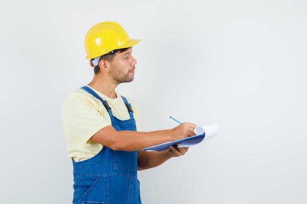 Jonge ingenieur die aantekeningen maakt terwijl hij aandachtig luistert in uniform vooraanzicht.