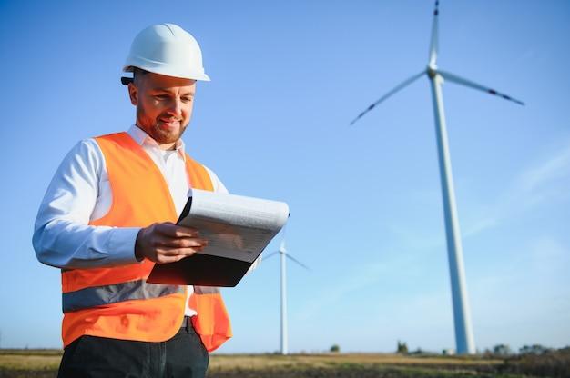 Jonge ingenieur die windturbines kijkt en controleert op het veld