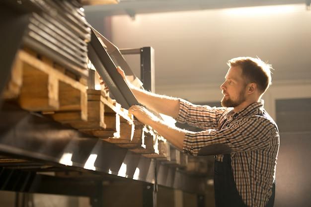 Jonge ingenieur geschikt reserveonderdeel voor industriële machine kiezen tijdens het werken in moderne fabriek