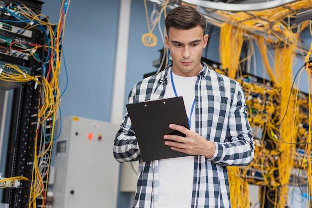 Jonge ingenieur in het middelgrote schot van de serverruimte