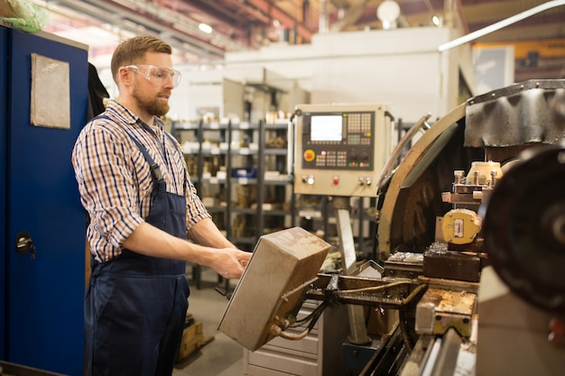 Jonge ingenieur in overall en beschermende bril permanent door industriële machine tijdens het werk