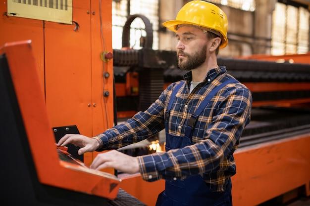 Jonge ingenieur in uniform en veiligheidshelm permanent door terminal tijdens het besturen van industriële machine