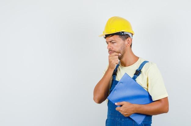 Jonge ingenieur in uniform klembord houden en denken, vooraanzicht.
