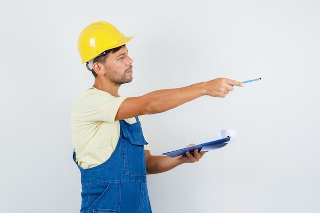 Jonge ingenieur in uniform klembord houden en wijzen naar kant, vooraanzicht.