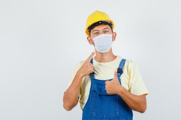Jonge ingenieur in uniform wijzend op masker met duim omhoog, vooraanzicht.