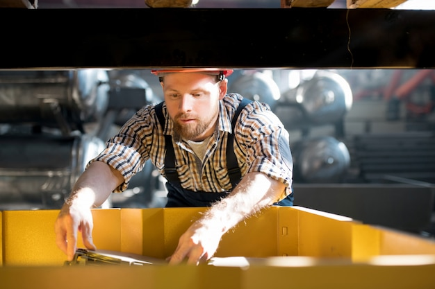 Jonge ingenieur in werkkleding leert principes van mechanisme werken tijdens het werken met technische apparatuur