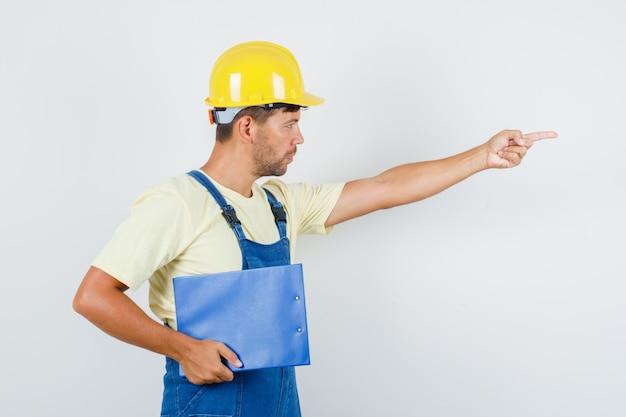 Jonge ingenieur klembord houden en wijzen naar kant in uniform vooraanzicht.