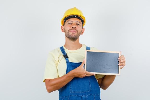 Jonge ingenieur met bord en lachend in uniform, vooraanzicht.