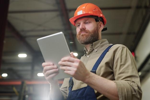 Jonge ingenieur met een rode baard die tablet voor zichzelf houdt terwijl hij tijdens het werk door online gegevens kijkt