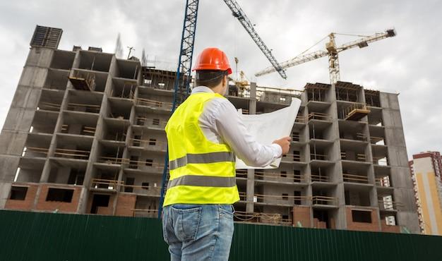 Jonge ingenieur op bouwplaats die plannen en blauwdrukken controleert checking