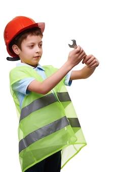 Jonge ingenieur reparateur in beschermende helm en vest met moersleutel op witte geïsoleerde achtergrond