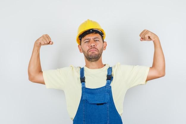 Jonge ingenieur spieren in uniform tonen en er sterk uitzien. vooraanzicht.