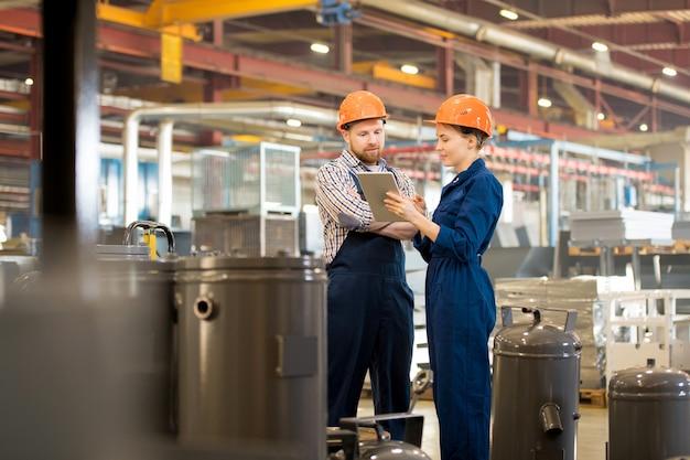 Jonge ingenieurs in overalls en helmen die in het net surfen om wat meer informatie te krijgen over industriële apparatuur