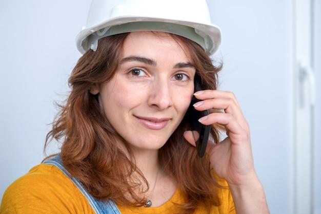 Jonge ingenieursvrouw met veiligheidshelm die op telefoon spreekt
