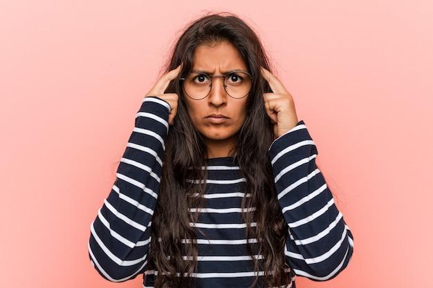Jonge intellectuele indiase vrouw concentreerde zich op een taak en hield hem met zijn wijsvinger op zijn kop.