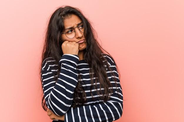 Jonge intellectuele indiase vrouw die zich verdrietig en peinzend voelt, kijkend naar kopie ruimte.