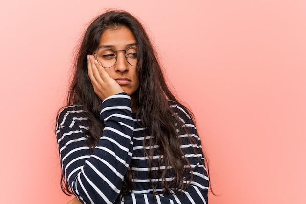Jonge intellectuele indiase vrouw die zich vervelen, vermoeide en behoefte aan een dag ontspannen.
