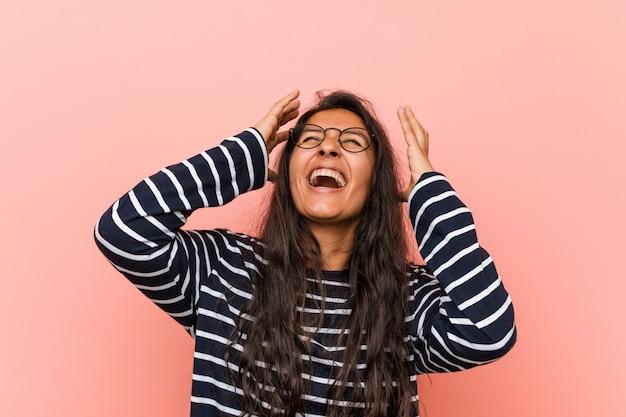 Jonge intellectuele indiase vrouw lacht vreugdevol handen op het hoofd te houden. geluk concept.