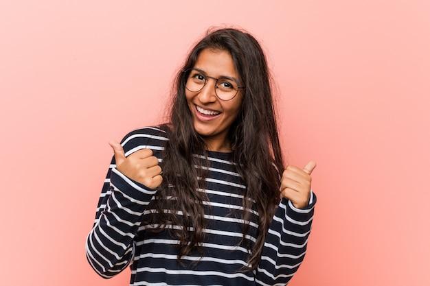 Jonge intellectuele indiase vrouw verhogen beide duimen omhoog, glimlachen en zelfverzekerd.