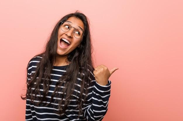Jonge intellectuele indiase vrouw wijst met duimvinger weg, lachend en zorgeloos.