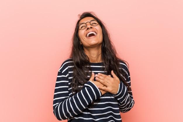Jonge intellectuele indische vrouw die houdend handen op hart, van geluk lachen.