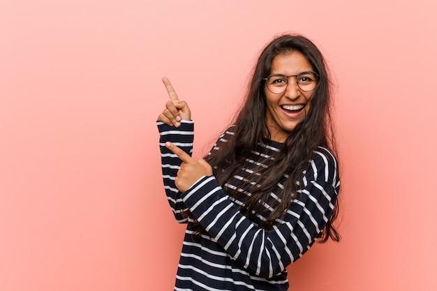 Jonge intellectuele indische vrouw die met wijsvingers aan een exemplaarruimte richt, die opwinding en wens uitdrukt.