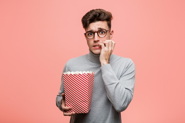 Jonge intellectuele mens die een popcornemmer houdt die vingers voor het hebben van geluk kruist