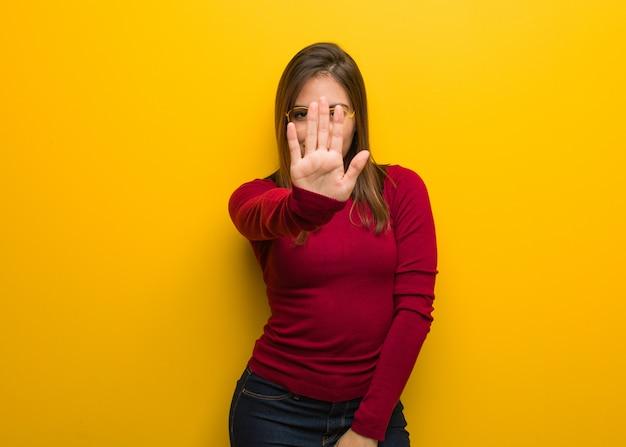 Jonge intellectuele vrouw die hand vooraan zet