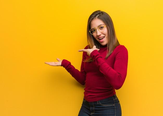 Jonge intellectuele vrouw die iets met hand houdt