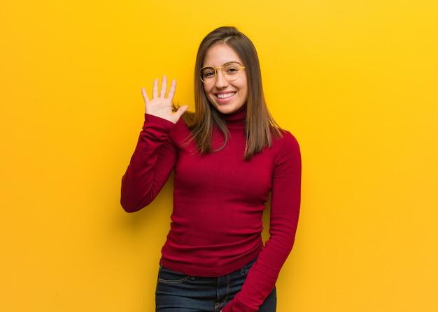 Jonge intellectuele vrouw die nummer vijf toont